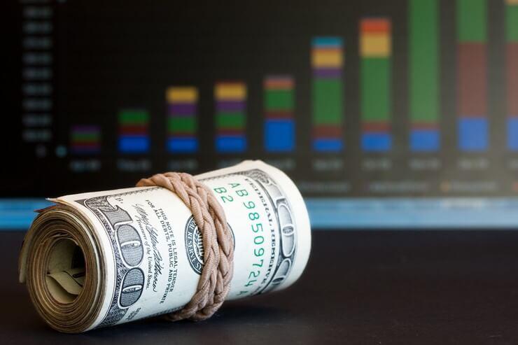 Пачка долларов на фоне котировок